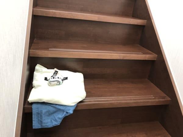 階段に服をおいている